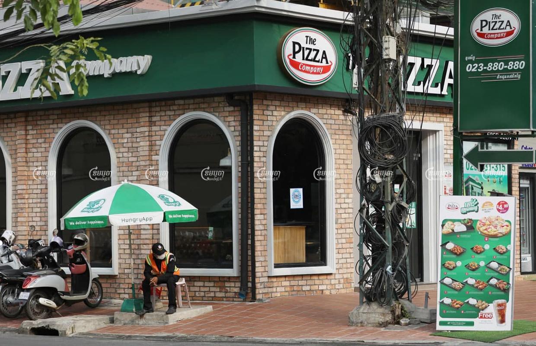 សន្តិសុខម្នាក់អង្គុយនៅមុខហាងភីហ្សាខមផេនី (Pizza Company ) នៅភ្នំពេញថ្ងៃទី ១៨ ខែមីនាឆ្នាំ ២០២១ ។ ខេមបូចា/ព្រីង សំរាំង